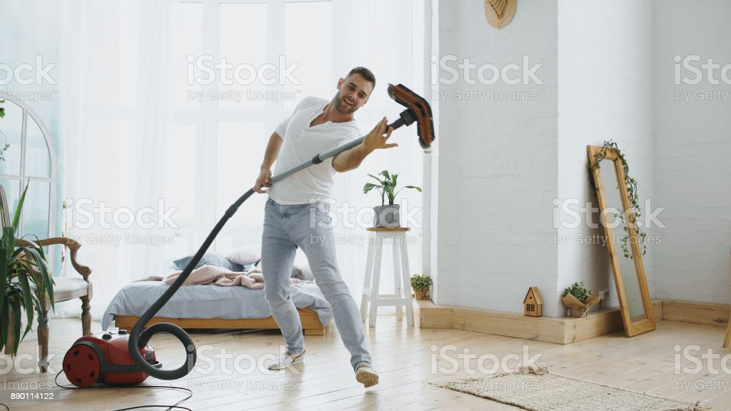 Young man having fun cleaning house with vacuum cleaner dancing stock photo