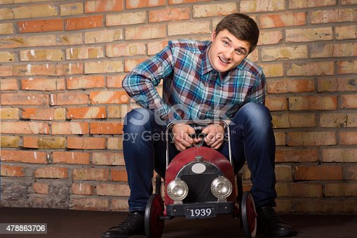 496487362istockphoto Young man having fun riding a toy truck 478863706