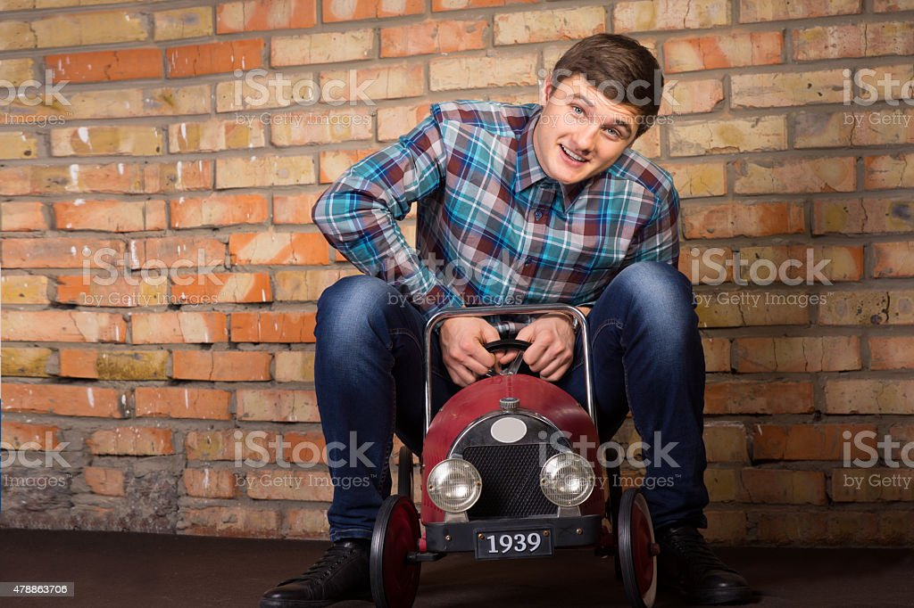 Young man having fun riding a toy truck stock photo
