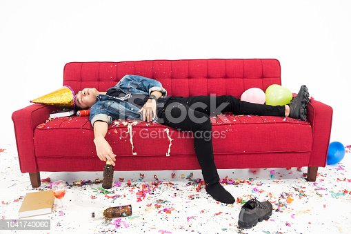 Young man having hangover after new year party, sleeping with chaos on red sofa
