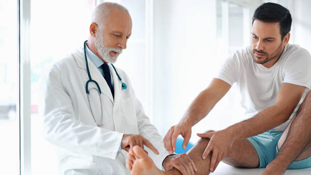 young man having his ankle examined. - old man feet stock photos and pictures