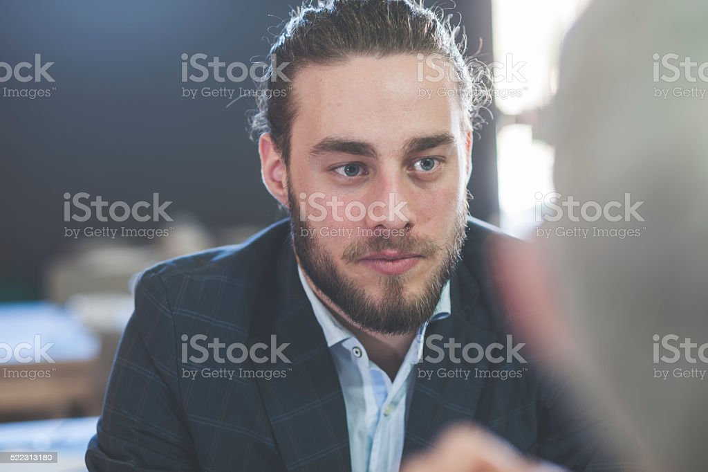 Young man having lunch at a restaurant with friends stock photo