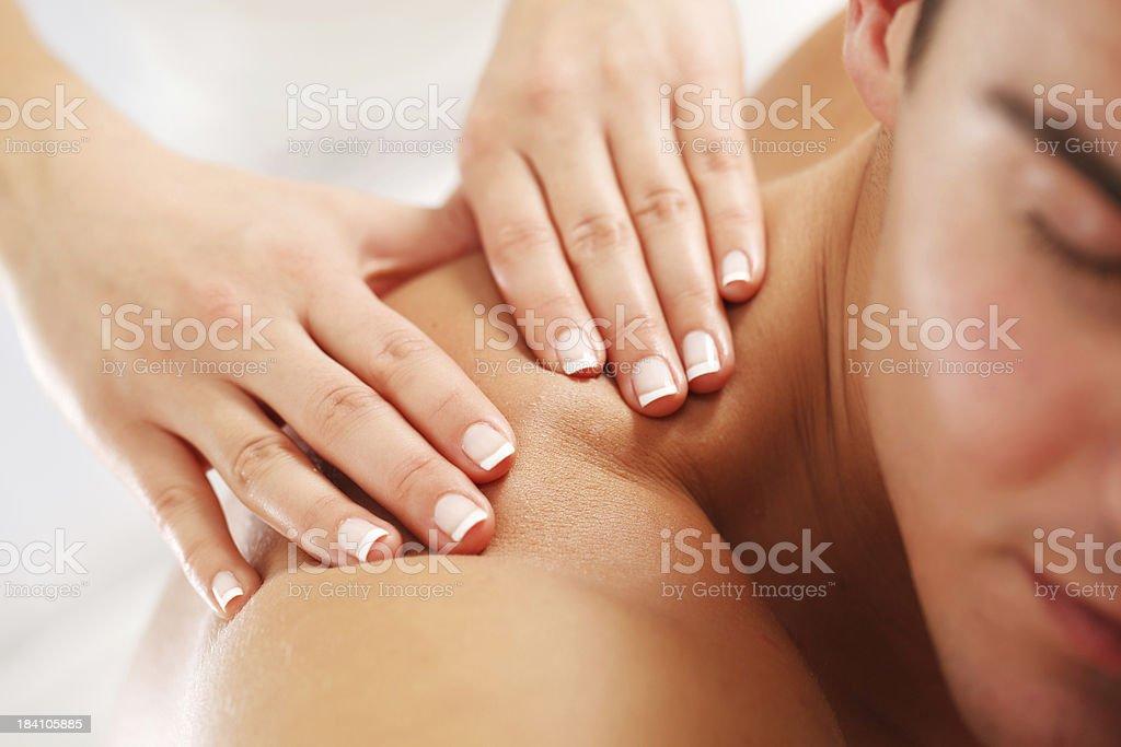 Young man having massage at the spa. stock photo
