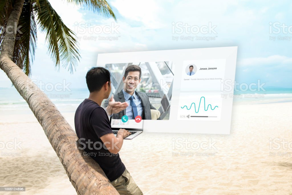 Young man having remote video conference call with manager at the beach