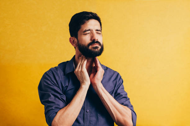 Young man having sore throat and touching his neck over yellow background. Hard to swallow Young man having sore throat and touching his neck over yellow background. Hard to swallow throat stock pictures, royalty-free photos & images