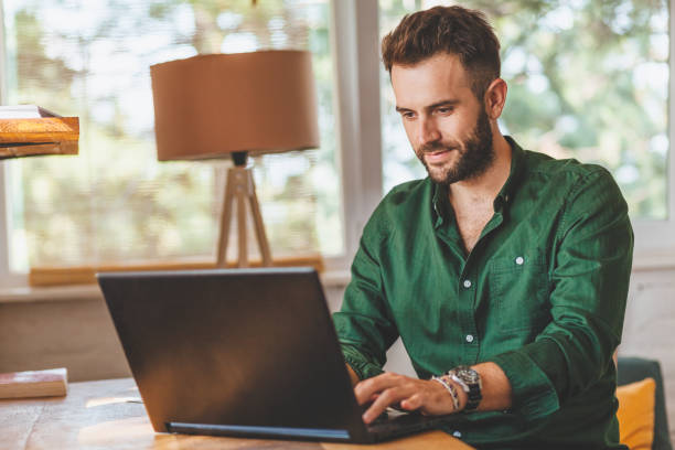 Young man having stressful time working on laptop stock photo