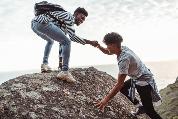 Young man helping his friend to climb the rock stock photo