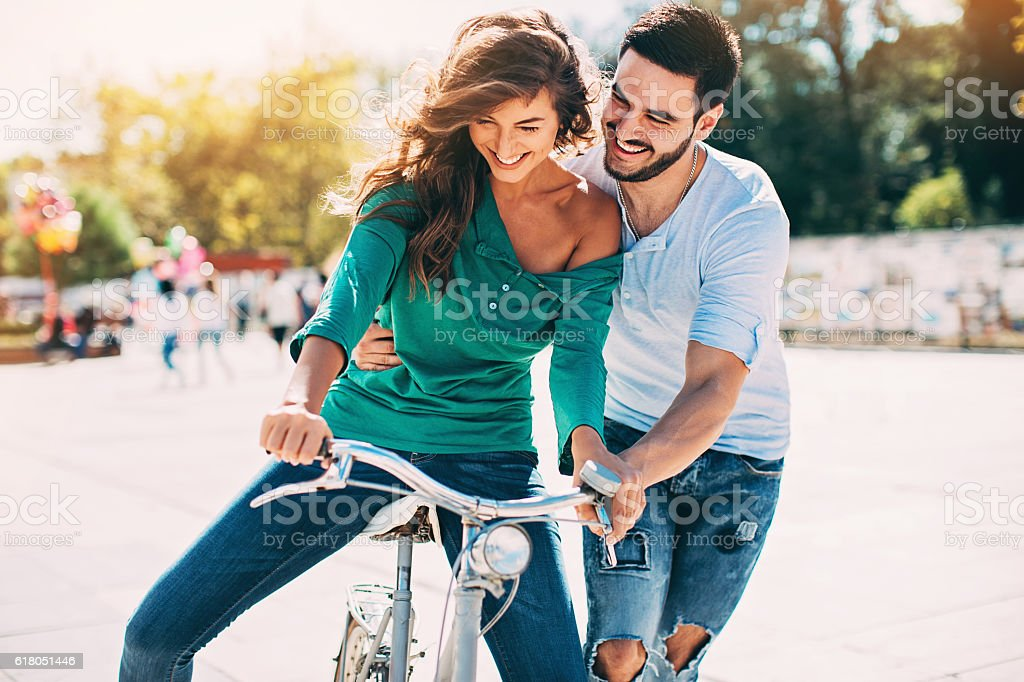 Young man helping his girlfriend to ride a bike stock photo