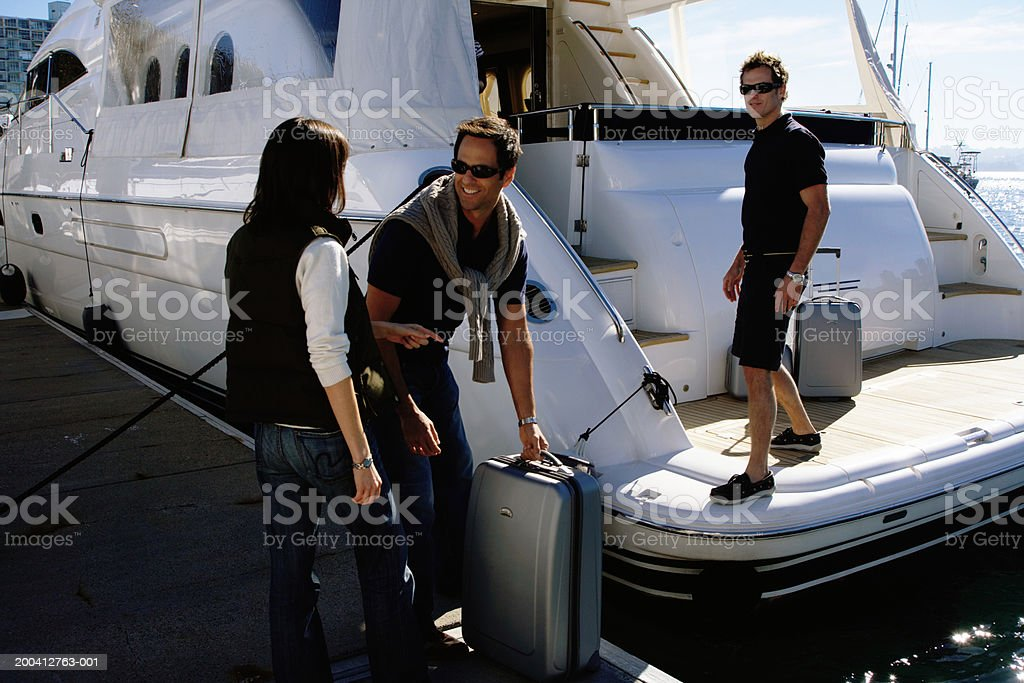 Young man helping load couple's luggage onto yacht in marina Sydney Harbour, Sydney Australia. 25-29 Years Stock Photo