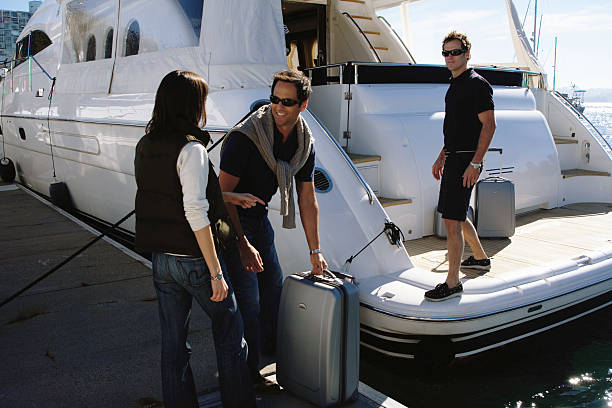 Young man helping load couple's luggage onto yacht in marina stock photo