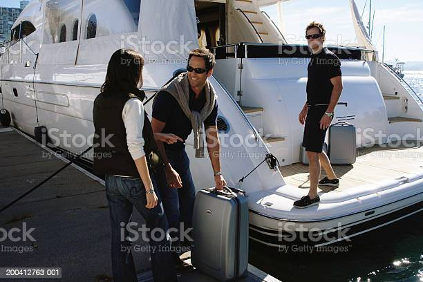 Young Man Helping Load Couples Luggage Onto Yacht In Marina Stock Photo - Download Image Now