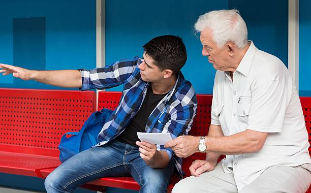 Young man helping retiree Horizontal view of young man helping retiree stranger stock pictures, royalty-free photos & images
