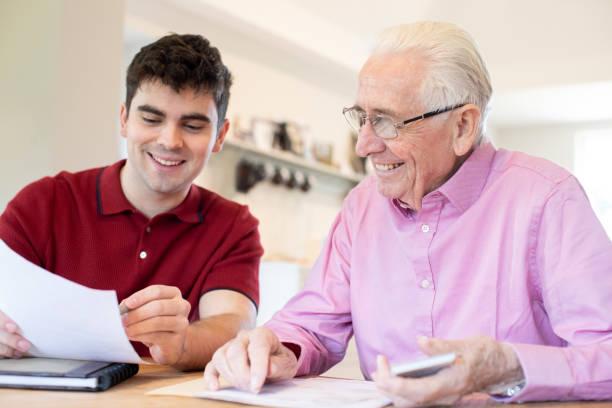 junger mann hilft senioren-nachbarn mit papierkram zu hause - einen gefallen tun stock-fotos und bilder