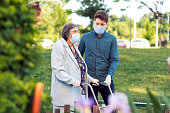 Young man helping his grandma walking around the neighborhood.They wearing protective facial mask and gloves.Senior woman using walker.