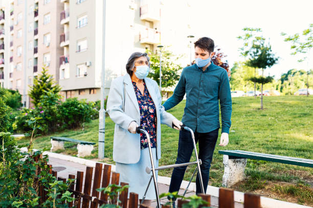 Young man helping senior woman walking in the street stock photo