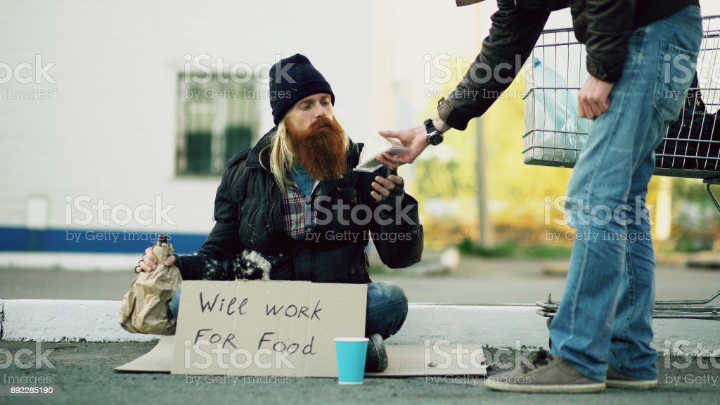 Young man helps to homeless person and giving him some food while beggar drink alcohol and sit near shopping cart at street stock photo