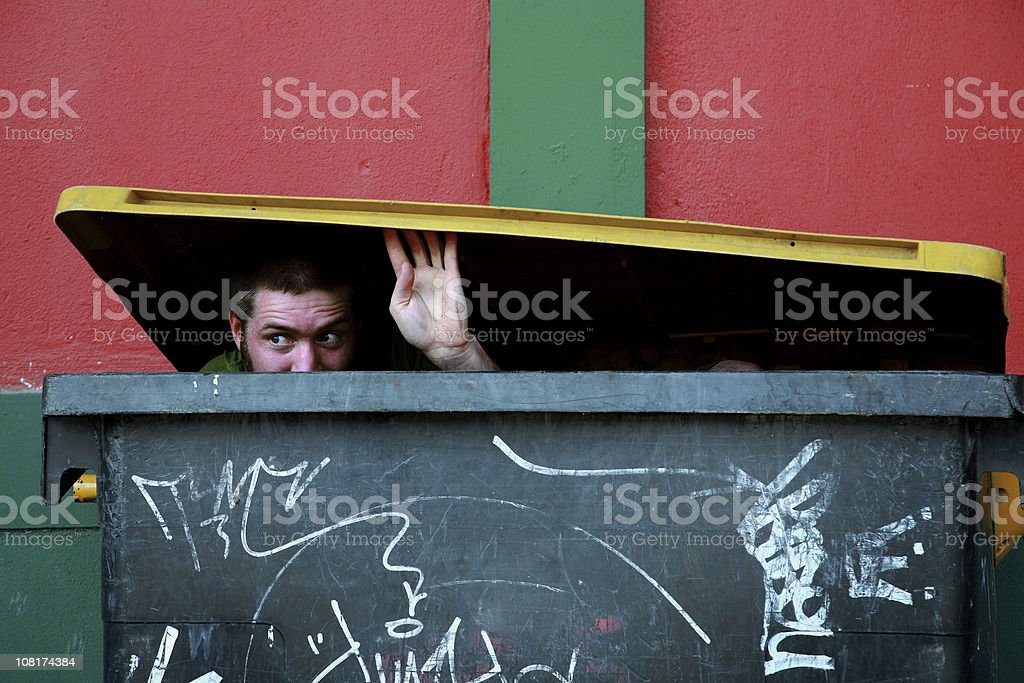 Young Man Hiding in Garbage Dumpster and Looking Out stock photo