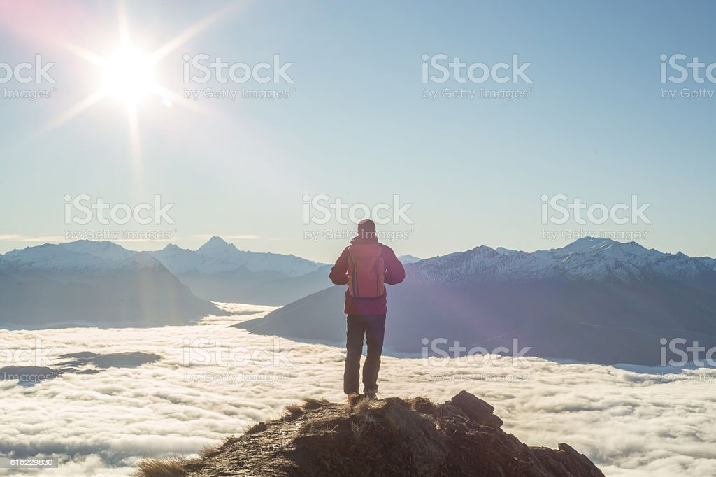 Young man hiker stands on mountain peak above clouds – Foto