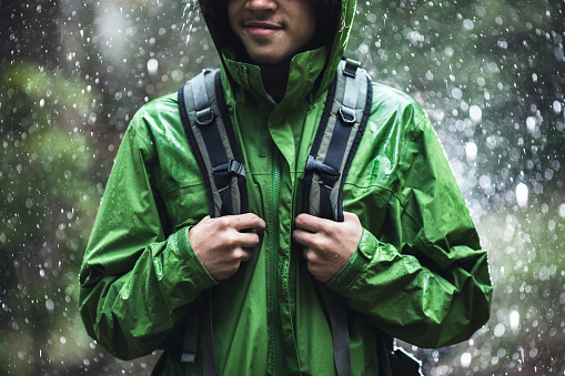 A cheerful young adult African American man goes for a hike in the rain in the Pacific Northwest, the raindrops repelling from his raincoat.  Shot in Washington state.