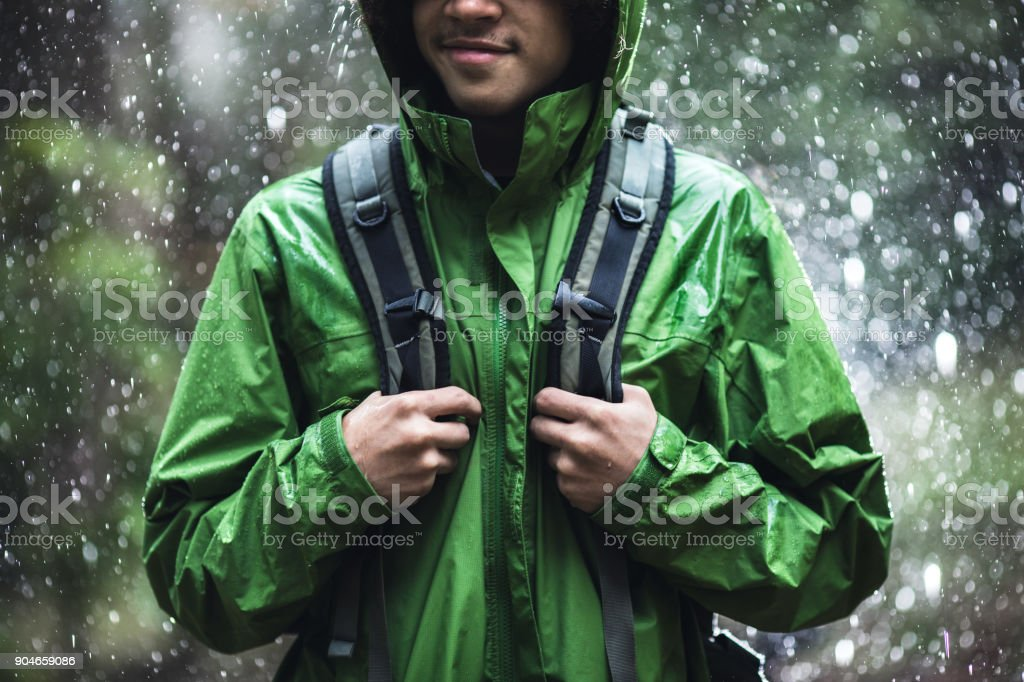 Young Man Hiking in Rain with Waterproof Jacket stock photo
