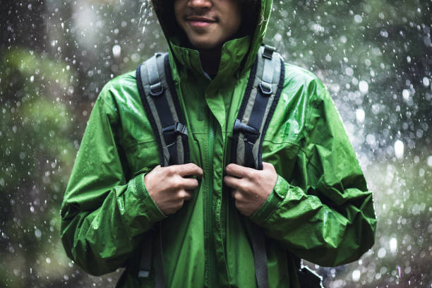 Young Man Hiking in Rain with Waterproof Jacket A cheerful young adult African American man goes for a hike in the rain in the Pacific Northwest, the raindrops repelling from his raincoat.  Shot in Washington state. waterproof clothing stock pictures, royalty-free photos & images