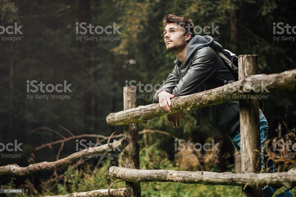 Young man hiking in the forest Young man with backpack hiking in the forest and leaning on a wooden fence, nature and physical exercise concept Adult Stock Photo