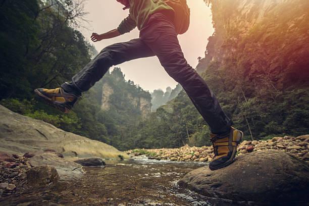 young man hiking jumps over the mountain river - der nächste schritt stock-fotos und bilder