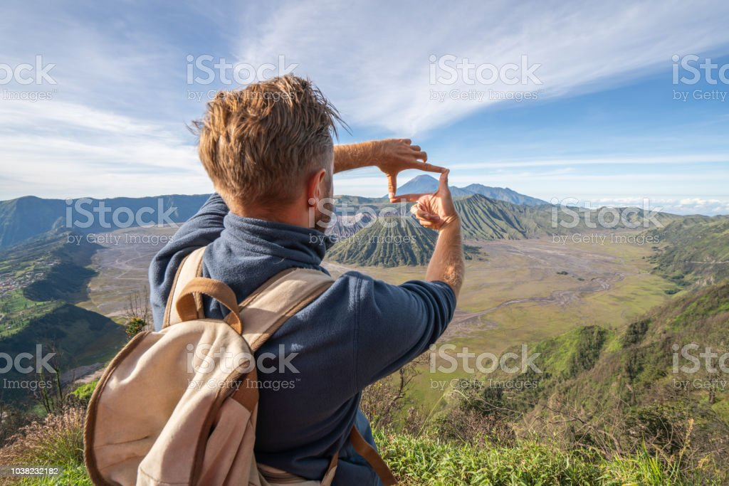 Young man hiking makes finger frame on volcanic landscape from top of hill looking at Bromo volcanoes- People travel adventure concept Young man hiking makes finger frame on volcanic landscape from top of hill looking at Bromo volcanoes- People travel adventure concept 20-29 Years Stock Photo