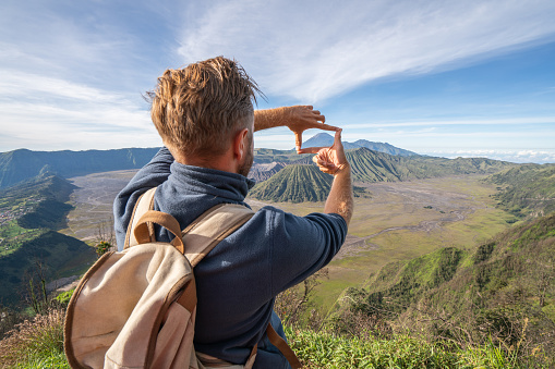 Young Man Hiking Makes Finger Frame On Volcanic Landscape From Top Of Hill Looking At Bromo Volcanoes People Travel Adventure Concept Stock Photo - Download Image Now