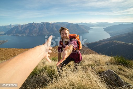 istock Young man hiking pulls out hand to get assistance 501292608