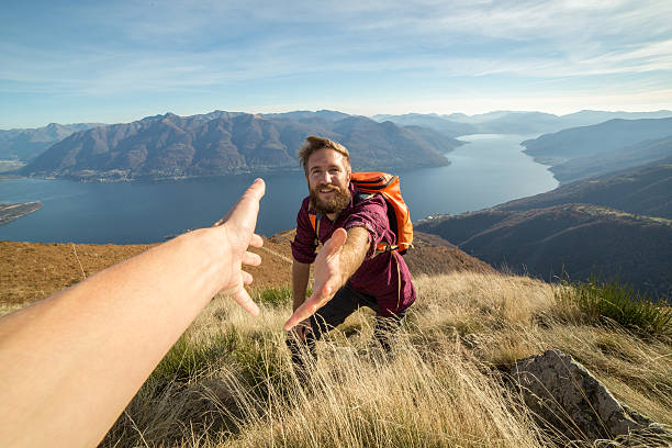 Young man hiking pulls out hand to get assistance stock photo