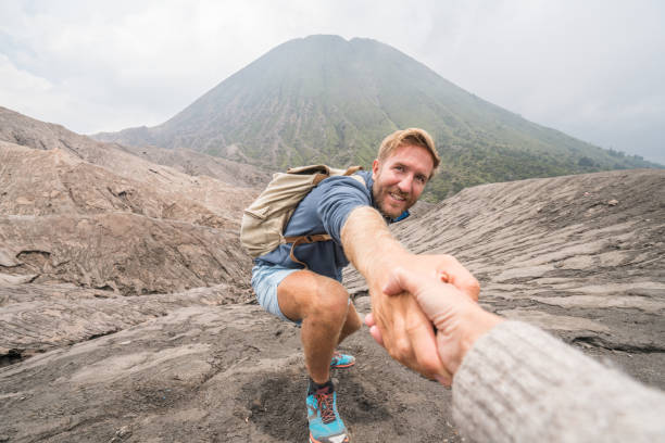 young man hiking, pulls out hand to reach the one of teammate. a helping hand to reach the top of crater volcano. bromo volcano region in indonesia, asia - przewodzić zdjęcia i obrazy z banku zdjęć