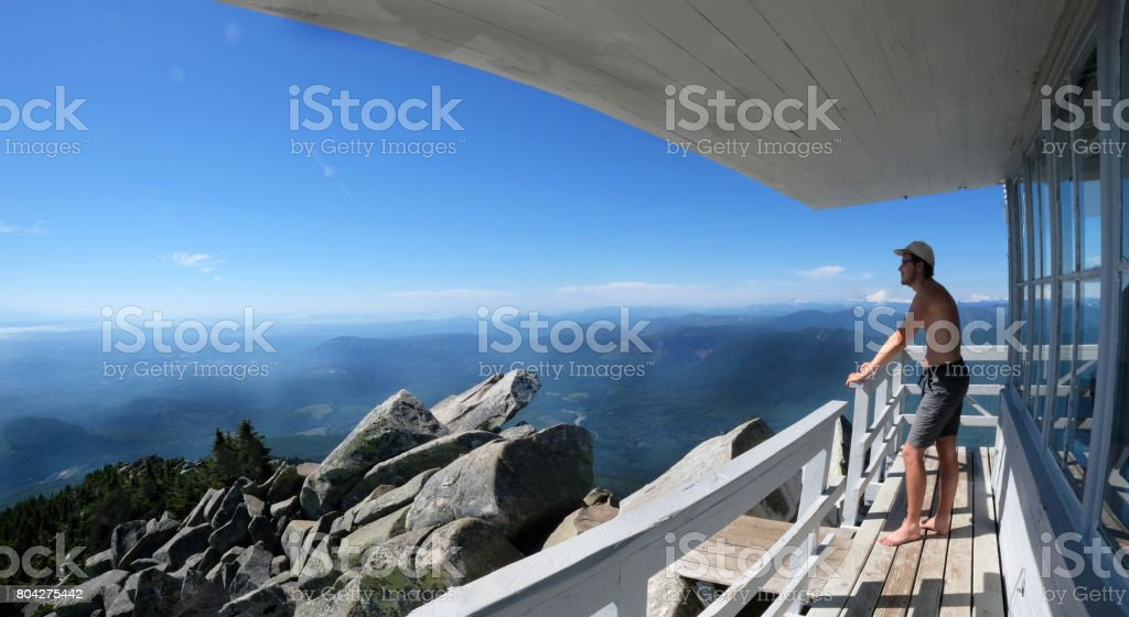 Young man hipster on mountain hut looking at views. Mount Pilchuck. Seattle. Washington. United States. stock photo