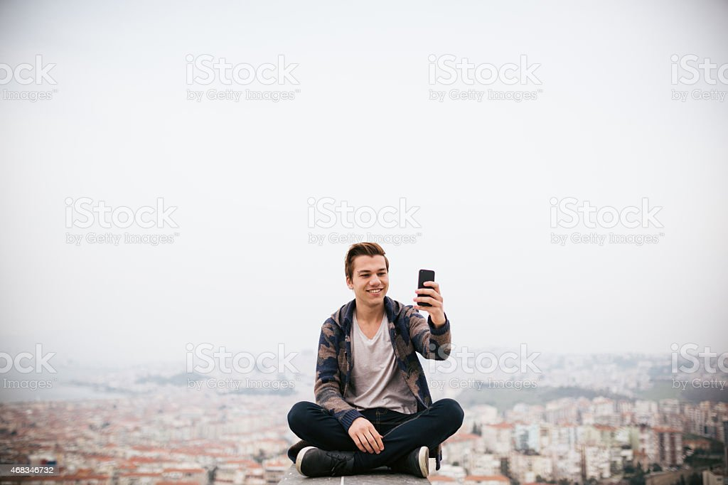 Young man his take photo sitting with cityscape stock photo