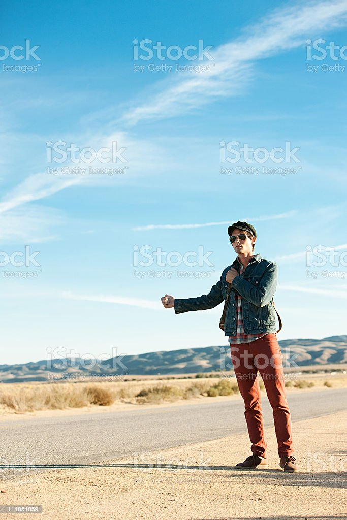 Young man hitchhiking at roadside stock photo