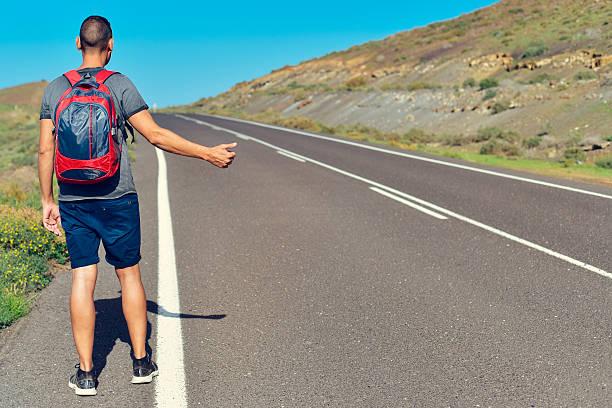 young man hitchhiking stock photo