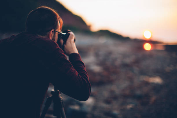 Young man holding a camera on a tripod and taking a picture of the sea. Gaspesie, Quebec, Canada stock photo