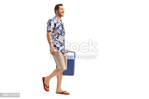 istock Young man holding a cooling box and walking 838107024