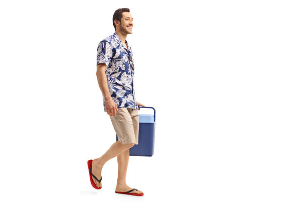 Young man holding a cooling box and walking stock photo