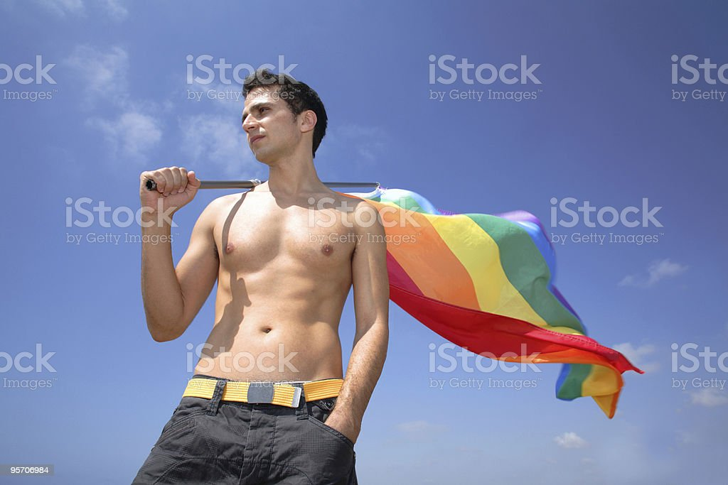 young man holding a gay pride rainbow flag royalty-free stock photo