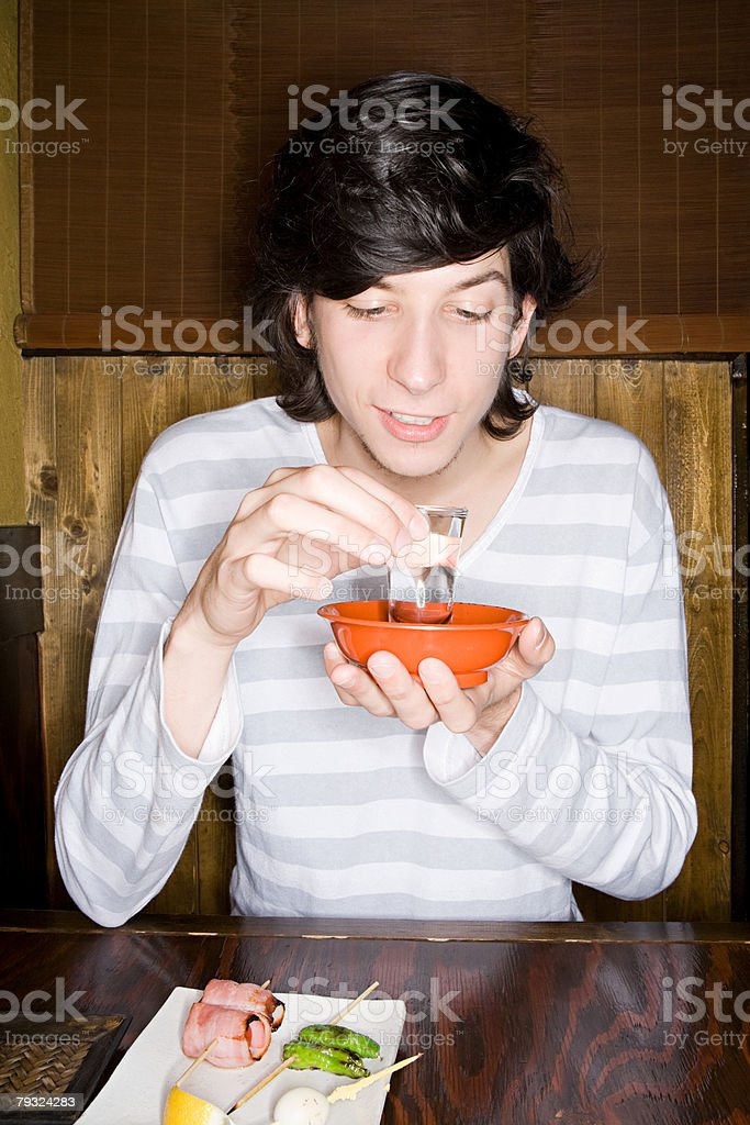 Young man holding a glass of sake royalty-free 스톡 사진