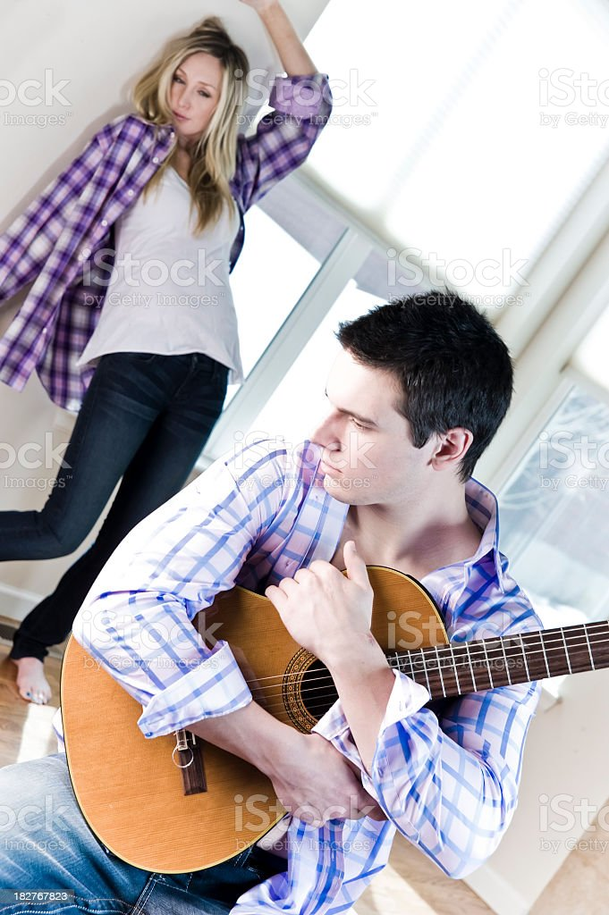 Young man holding a guitar with healthy woman in background stock photo