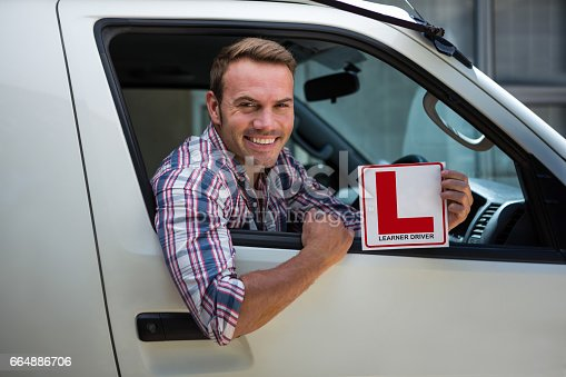1051147634 istock photo Young man holding a learner driver sign 664886706