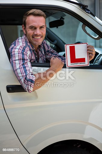 1051147634 istock photo Young man holding a learner driver sign 664888770