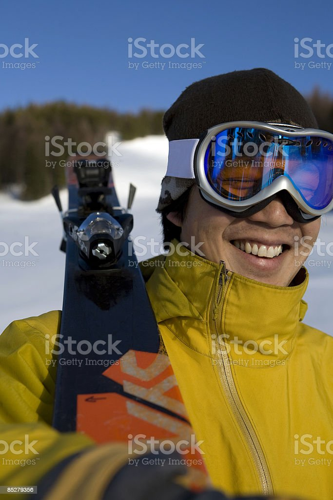 A young man holding a pair of skis. royalty-free stock photo