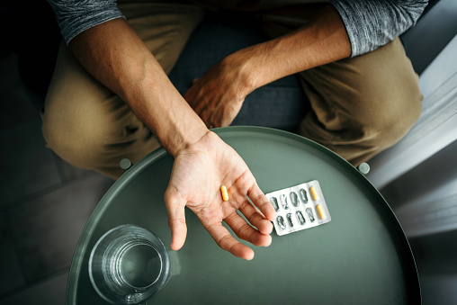Young man holding a pill in his hand. Medical treatment / drug use concept. Illness/ health problems concept.