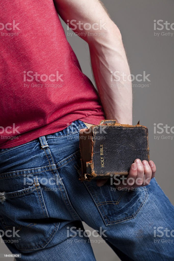 Young man holding a worn Bible behind his back royalty-free stock photo