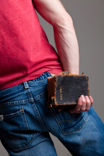 Young man holding a worn Bible behind his back