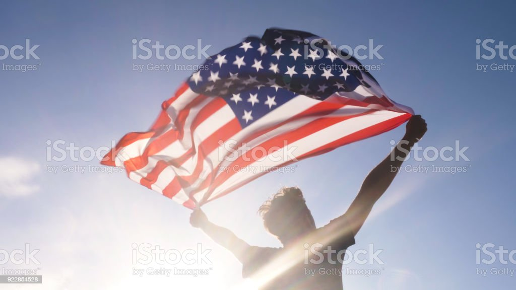 Young man holding american national flag to the sky with two hands at the beach at sunset usa stock photo