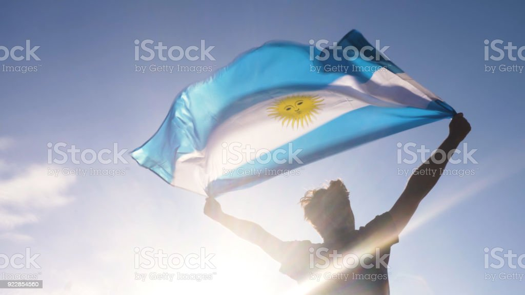 Young man holding argentinian national flag to the sky with two hands at the beach at sunset argentina stock photo